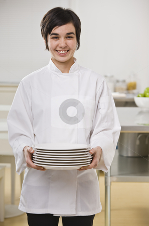 Woman Holding Stack of Dishes stock photo, A woman is holding a stack of dishes and smiling at the camera.  Vertically framed shot. by Jonathan Ross