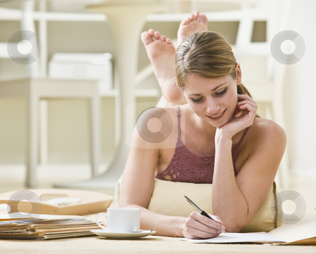 Woman Writing on Files stock photo, A young woman is laying on her stomach and working on paperwork.  She is looking away from the camera.  Horizontally framed shot. by Jonathan Ross