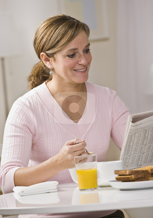 Woman Eating Breakfast stock photo, A young woman is eating breakfast and reading a newspaper.  She is smilign at the camera.  Vertically framed shot. by Jonathan Ross