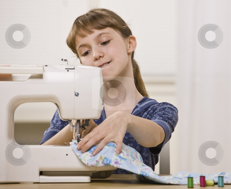 Girl on Sewing Machine stock photo, A young girl is sewing on a sewing machine.  She is looking away from the camera.  Horizontally framed shot. by Jonathan Ross