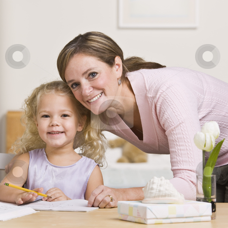Woman Sitting with Daughter stock photo, A mother is sitting with her young daughter and watching her draw.  They are smiling at the camera.  Square framed shot. by Jonathan Ross