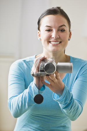 Woman with Camcorder stock photo, A woman is holding a camcorder and smiling at the camera.  Vertically framed shot. by Jonathan Ross