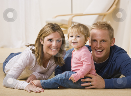 Young Family Smiling stock photo, A beautiful and young couple pose with their young daughter as they all smile at the camera.  Horizontally framed shot. by Jonathan Ross