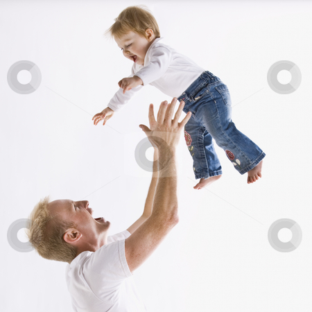 Father Playing with Daughter stock photo, A young father is playing with his daughter and throwing her up in the air.  They are smiling at each other.  Square framed shot. by Jonathan Ross