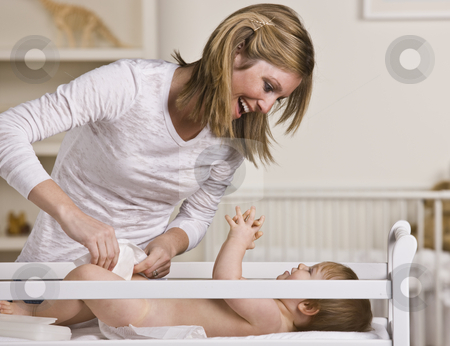 Woman Changing Baby stock photo, A young mother is changing her baby's diaper.  She is smiling and looking at her baby.  Horizontally framed shot. by Jonathan Ross