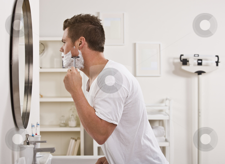 Man Shaving Face stock photo, A young man is shaving his face in front of the bathroom mirror.  He is looking away from the camera.  Horizontally framed shot. by Jonathan Ross