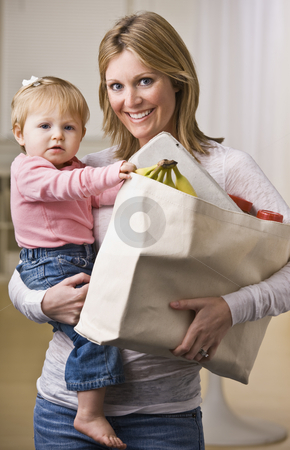 Mother Holding Daughter and Groceries stock photo, A young mother is holding her daughter in one arm and a bag of groceries in the other.  She is smiling at the camera.  Vertically framed shot. by Jonathan Ross