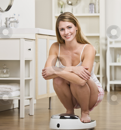 Woman Crouching on Scale stock photo, A young woman is crouching on a bathroom scale and checking her weight.  She is smiling at the camera.  Square framed shot. by Jonathan Ross