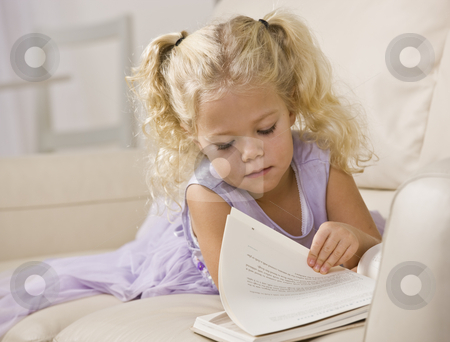 Little Girl Reading Book stock photo, A beautiful little girl lying on a couch and reading a book.  Horizontally framed shot. by Jonathan Ross