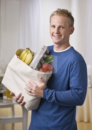 Man Holding Groceries stock photo, A young man is holding a sack of groceries and smiling at the camera.  Vertically framed shot. by Jonathan Ross
