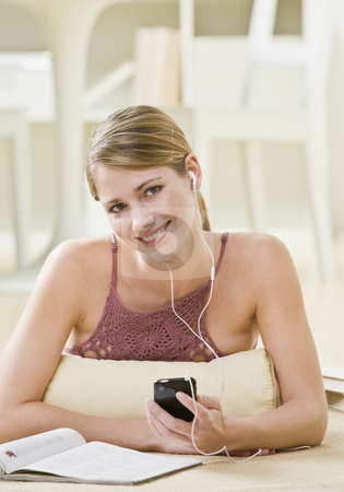 Woman Listening to Music stock photo, A young woman is laying down and listening to an MP3 player.  She is smiling at the camera.  Vertically framed shot. by Jonathan Ross