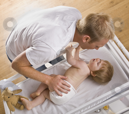 Man Changing Baby stock photo, A young father is changing his baby daughter's diaper.  They are looking at each other.  Square framed shot. by Jonathan Ross