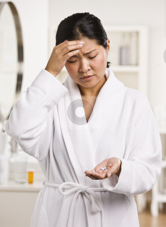 Woman with Headache stock photo, A young woman is holding pain medication that she is about to take for a headache.  She is looking away from the camera.  Vertically framed shot. by Jonathan Ross