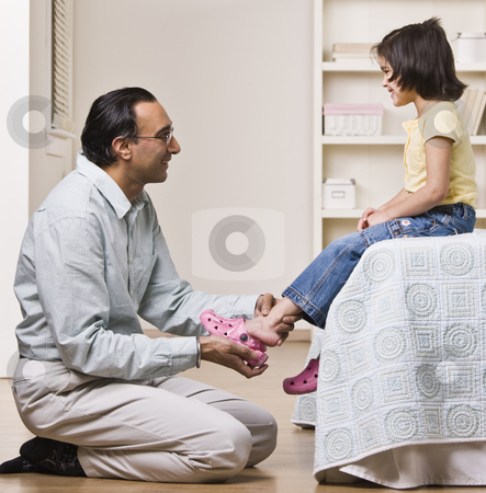 Father Helping Daughter with Shoes stock photo, A father is helping his baby daughter with her shoes.  They are smiling and looking each other.  Square framed shot. by Jonathan Ross
