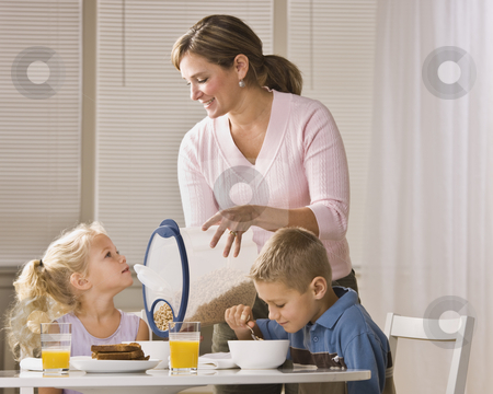Family Eating Breakfast stock photo, A beautiful family eating breakfast together. The mother is smiling and is pouring cereal for the daughter.  Horizontally framed shot. by Jonathan Ross