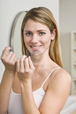 Woman Flossing Teeth stock photo, A young woman is about to floss her teeth.  She is smiling at the camera.  Vertically framed shot. by Jonathan Ross