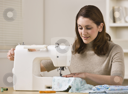 Woman Using Sewing Machine stock photo, An attractive brunette sewing in her home.  She has a slight smile on her face.  Horizontally framed shot. by Jonathan Ross