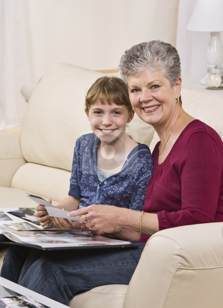 Grandmother and Granddaugter looking through album stock photo, A grandmother is seated on a couch with her granddaughter and they are looking through a wedding album.  They are smiling at the camera.  Vertically framed shot. by Jonathan Ross