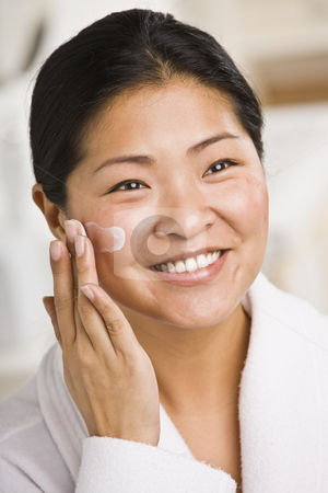 Woman Applying Facial Cream stock photo, A smiling woman applies facial cream.  She is looking away from the camera.  Vertically framed shot. by Jonathan Ross