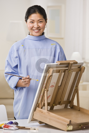 Woman Painting Picture stock photo, A woman is painting a picture on an easel.  She is smiling at the camera.  Vertically framed shot. by Jonathan Ross