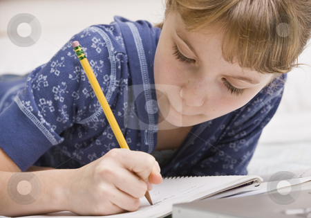 Young Girl Writing stock photo, A young girl writing in a notebook.  Horizontally framed shot. by Jonathan Ross