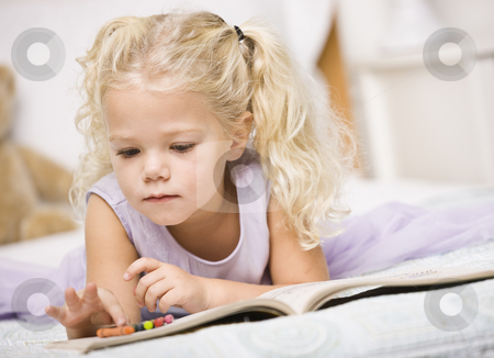 Girl Coloring in Books stock photo, A young girl is laying on a bed and coloring in books.  She is looking away from the camera.  Horizontally framed shot. by Jonathan Ross