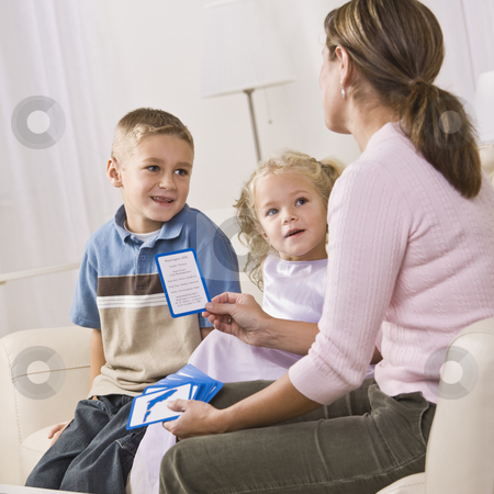 Mother Playing with Children stock photo, A mother is playing cards with her children.  They are smiling and looking at her.  Vertically framed shot. by Jonathan Ross