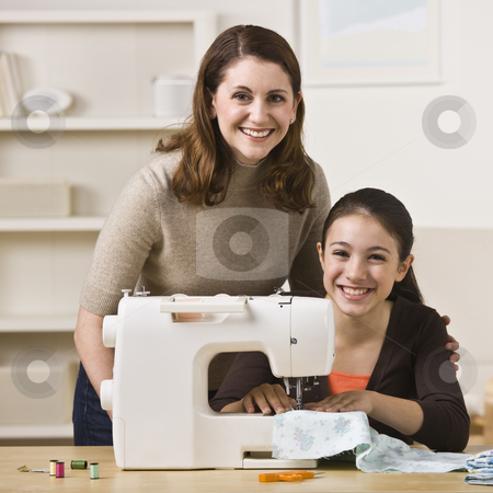 Mother and Daughter Sewing stock photo, A beautiful young girl sewing with her mother.  They are smiling at the camera.  Square framed shot. by Jonathan Ross