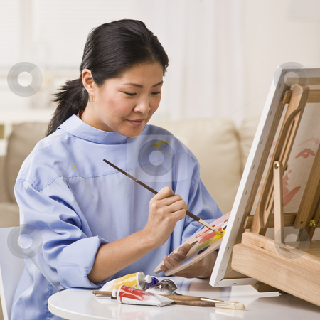 Woman Painting Picture stock photo, A woman is painting a picture on an easel.  She is looking away from the camera.  Square framed shot. by Jonathan Ross