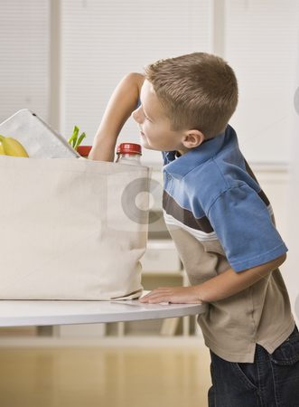 Boy Getting into Groceries stock photo, A young boy is getting into the grocery sack on the kitchen counter.  He is looking away from the camera.  Vertically framed shot. by Jonathan Ross