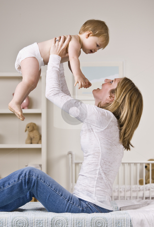 Mother Holding Baby stock photo, A young mother is sitting on a bed and holding up her baby girl.  They are smiling at each other.  Vertically framed shot. by Jonathan Ross