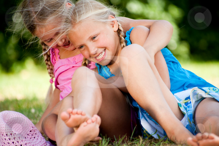 Playfull twins stock photo, Two little girls in fresh colors in the park by Frenk and Danielle Kaufmann