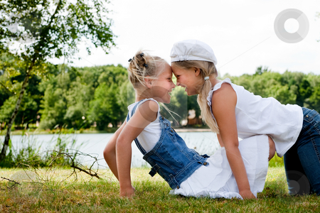 Crawling over my twinsister stock photo, Two little girls in fresh colors in the park by Frenk and Danielle Kaufmann
