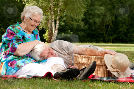 Grandmother is tickling grandfather stock photo, Elderly couple enjoying the spring in the park by Frenk and Danielle Kaufmann