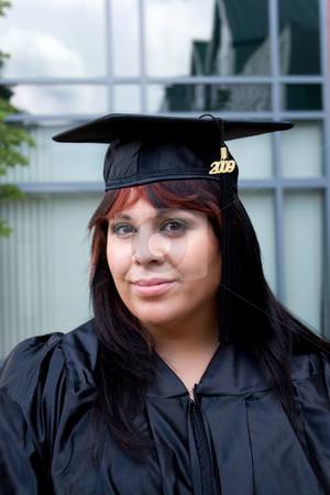 Young Woman Graduating stock photo, A recent graduate posing in her cap and gown. by Todd Arena