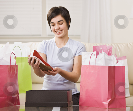 Cute brunette with shoes stock photo, Cute brunette woman surrounded by shopping bags and looking at new shoes. Horizontal. by Jonathan Ross
