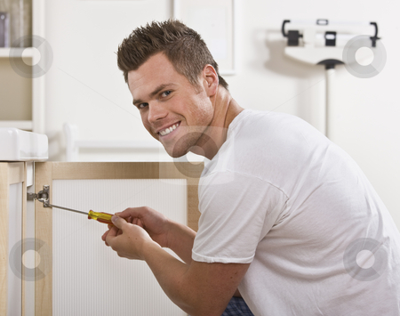 Smiling Man Fixing Cabinet Door stock photo, A man is fixing the cabinet door in his bathroom.  He is smiling at the camera.  Square framed shot. by Jonathan Ross