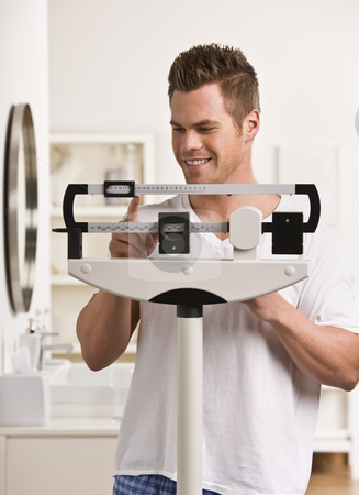 Attractive male on scale. stock photo, Attractive male weighing himself on scale and smiling. Vertical by Jonathan Ross
