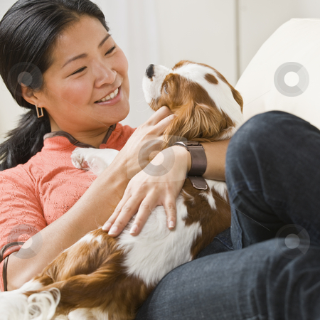 Asian woman with puppy. stock photo, Smiling Asian woman with puppy on her lap. Square. by Jonathan Ross