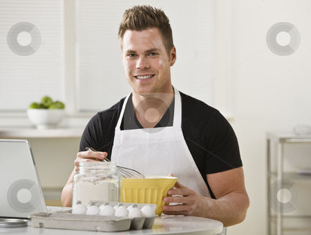 Man Mixing Ingredients in Kitchen stock photo, A young man with flour on his face is mixing ingredients in his kitchen.  He is smiling at the camera.  Horizontally framed shot. by Jonathan Ross