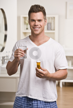 Attractive male with water and pills stock photo, Attractive male holding pill container and water, smiling at camera. Vertical by Jonathan Ross