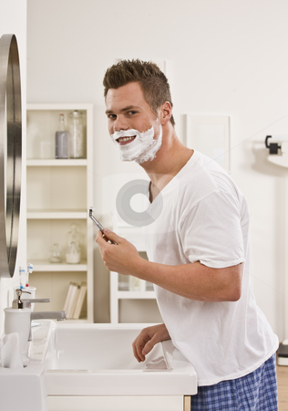 Man Shaving stock photo, A man is shaving his face in front of the bathroom mirror.  He is smiling at the camera.  Vertically framed shot. by Jonathan Ross
