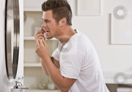 Man Flossing Teeth stock photo, A young man is flossing his teeth in front of the bathroom mirror.  He is looking away from the camera.  Horizontally framed shot. by Jonathan Ross