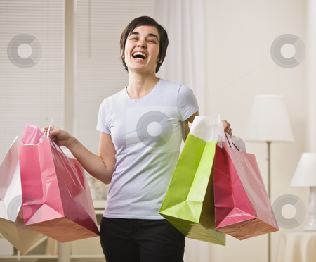 Smiling woman with shopping bags. stock photo, Woman with multi-colored shopping bags, smiling for the camera. Horizontal. by Jonathan Ross