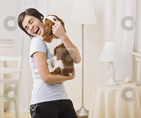 Woman Holding Dog stock photo, A woman is holding a puppy in her arms and laughing.  Horizontally framed shot. by Jonathan Ross