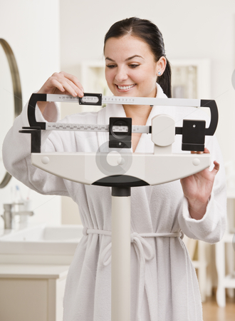 Smiling brunette on scale. stock photo, Smiling brunette weighing herself and smiling. Vertical by Jonathan Ross