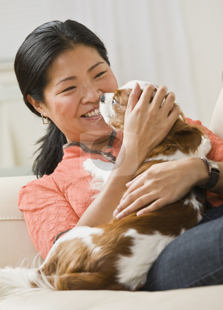Woman Cuddling Dog stock photo, A woman is holding a dog in her arms, smiling, and looking away from the camera.  Vertically framed shot. by Jonathan Ross