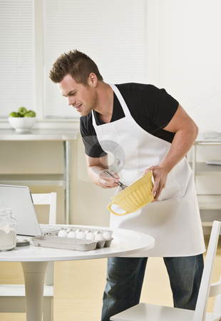 Attractive male with mixing bowl stock photo, Attractive male cooking with mixing bowl and looking at laptop. Vertical by Jonathan Ross