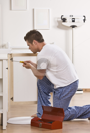Attractive male with screwdriver. stock photo, Attractive male kneeling and fixing cabinet door with screwdriver. Vertical by Jonathan Ross
