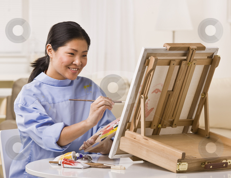 Asian woman painting stock photo, Asian woman sitting at table, smiling and painting on small easel. Horizontal by Jonathan Ross